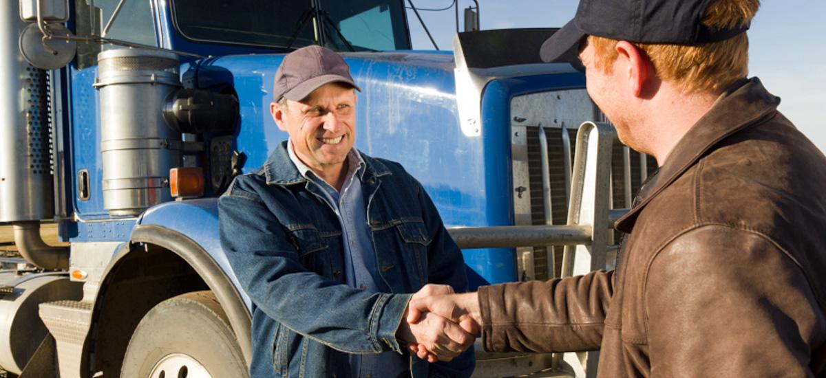 two men shaking hands in frront of blue trailer truck