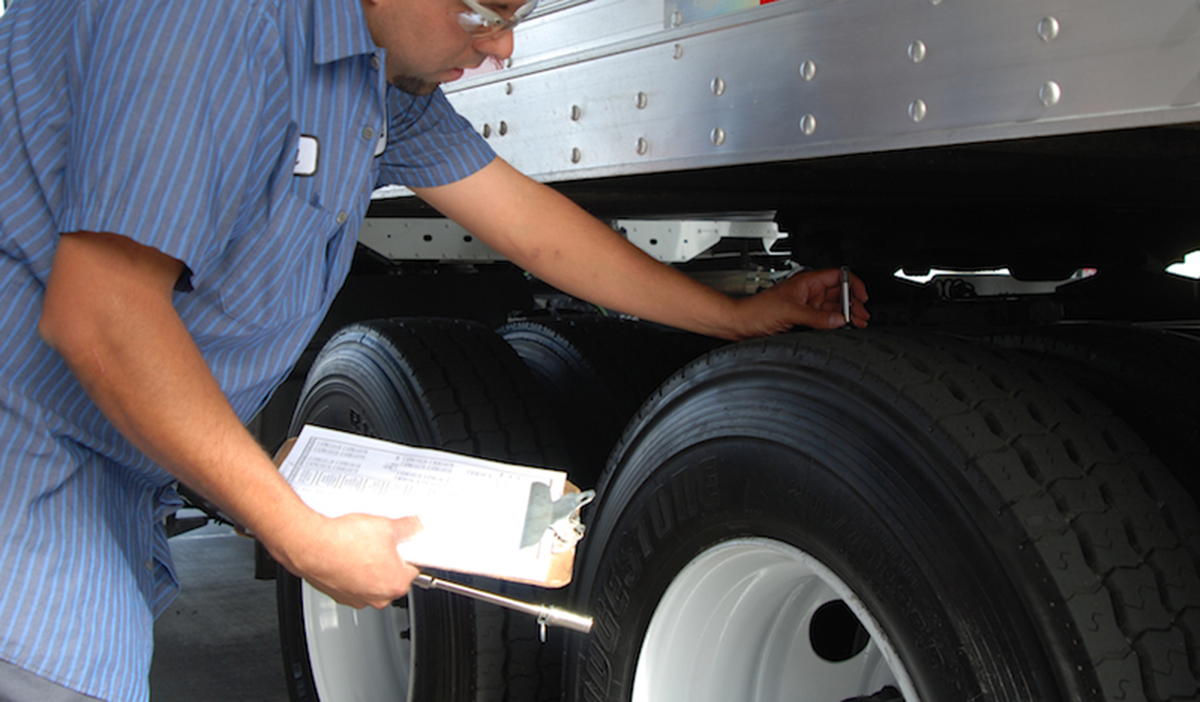 driver inspecting his tire