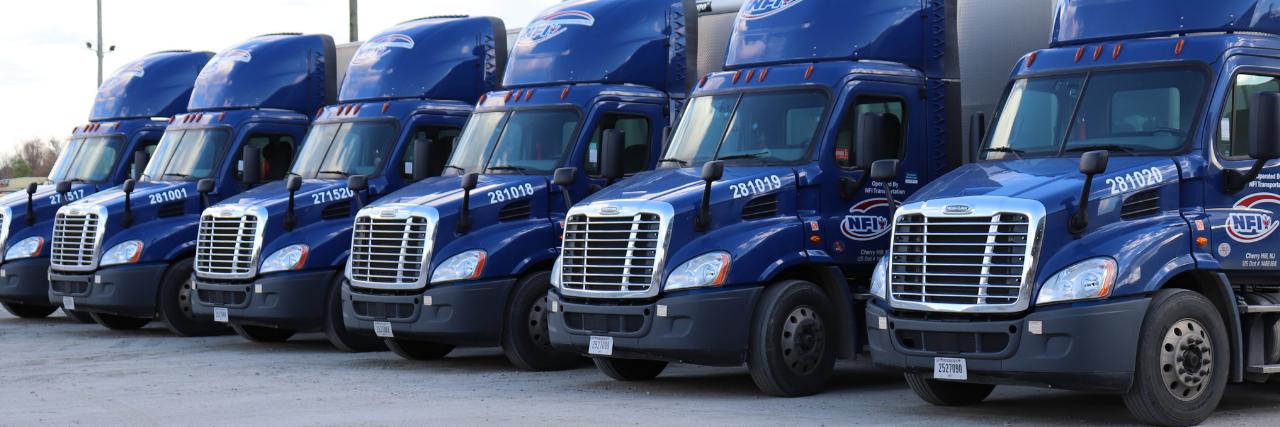 front of multiple blue trailer trucks