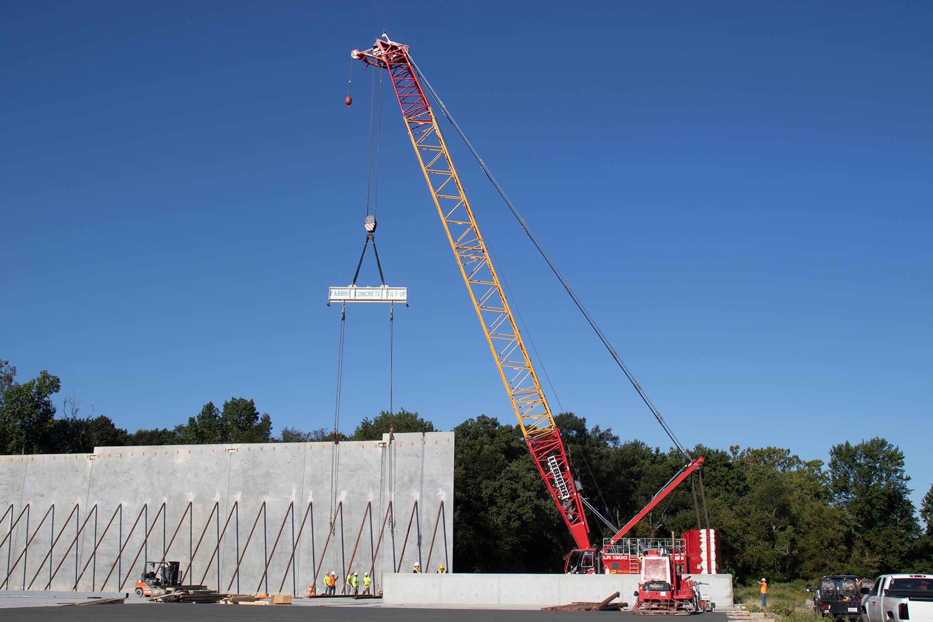 crane lifting sign above construction wall