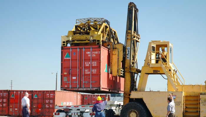 workers loading container on truck